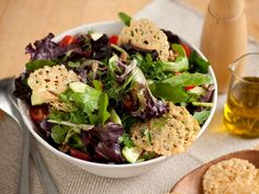 Mixed Green Salad with Parmigiano Crisps : Crisp rounds of baked Parmesan cheese take this salad to the next level. The greens are tossed with mixed herbs, tomato, onion and cucumber, then drizzled with olive oil and red wine vinegar.