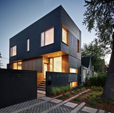 MODERNest and Kyra Clarkson Architect have designed a home showcasing a dark wood facade beautifully contrasting neighboring homes. Windows shape an idea of the interiors and illuminate surroundings at night as if the house were a lighthouse. Built in the West Queen West neighborhood of Toronto, Canada, the dark modern home is topped off with a green roof and deck. This allows owners to enjoy uninterrupted panoramic views of the city's skyline in a fresh, open environment.