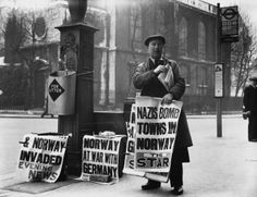 A newspaper seller with posters of headlines announcing the German invasion of Norway, 1940.