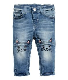 5-pocket jeans in washed stretch denim. Adjustable elasticized waistband, fly with snap fastener, and embroidery and appliqués on knees.