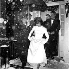 Jacqueline Kennedy lifts the skirt of her ivory double-faced silk satin twill inaugural ball gown, designed by Oleg Cassini, as she and President-elect John F. Kennedy leave their Georgetown home. They were en route to the inaugural concert in Washington, D.C., on Jan. 19, 1961. by fanny