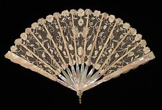 This is probably a child's fan but worked with very fine materials. The needle-made lace of the leaf is handmade and the placement of the motifs indicates it is made precisely for a fan of this size and shape; particularly charming is the melon shape beneath the two flowers at the center of the leaf.  fourth quarter 19th century