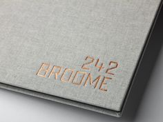 242 Broome Sales Center Book — Designed by And Partners, Produced by Brilliant.   DETAILS 9″x12″ finished size Smythe Sewn Text pages printed 6 color (CMYK plus two pantone spot colors). Case bound in Natuur & Halflinnen fabric. Copper foil debossing on front cover Includes two 5″x12″ short leaf pages Pages gilded in Black