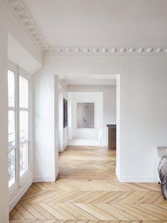 Gorgeous all-white interior with blonde wood herringbone floors and crown mouldings, all ready to be decorated with the interior decor picks of your design dreams! How would you design this space?