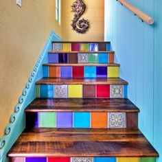 Eclectic staircase in Tampa. Stair risers are Spanish tiles in a random pattern. Yellow and blue walls. Wall trim carved into waves. Seahorse decoration.