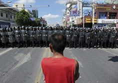 A protester stands in front of a lines of riot police officers Saturday July 28, 2012 in Qidong, Jiangsu Province, China. AP
