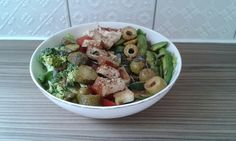 Smoked tofu salad bowl. Layer lettuce, broccoli, sliced broccoli stalk, pickled cucumber, tomato, olives, spring onion and avocado. Top with sesame smoked tofu and a spoon of humous. Sprinkle with chilli flakes and flax.