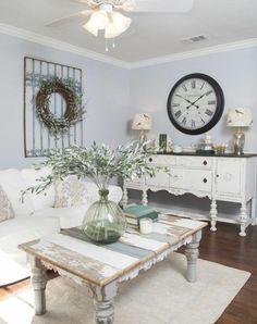 table campagne chic bois brut usé, tapis blanc, parquet marron, canapé blanc et meuble de rangement vintage, horloge retro, couronne de fleurs decorative