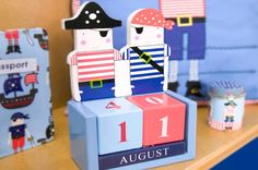 Pirate Wooden Calendar  Cute wooden calendar in the pirate theme. Calendar is blue with two beautifully painted pirates. Easy to change; the two date squares are red and pale blue and the month blocks are navy. | Childrens Bed Centres