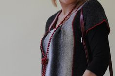 This gray and white striped tunic is knitted from woolen yarn, and a red contrast piping is used to define the seam, and style the lines of the garment. The piping used is with red handmade crochet ribbon. It has one big pocket which is also bordered with red crochet ribbon. There are two inverted pleats on the chest of the tunic stitched with the same red crochet ribbon. Ideally this tunic looks better when worn loosely and it looks nice over jeans and leggings.  The tunic is available in…
