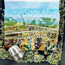 Sewing tiny beads onto another small fabric landscape.