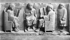 A Roman school. Two boys are reading scrolls. The boy on the right is trying to catch the teacher's eye. Perhaps he wants to go home