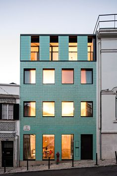 The green-tiled facade of this Lisbon townhouse by Camarim Arquitectos has varying textures and opacities designed to reference the building that previously stood on the site.