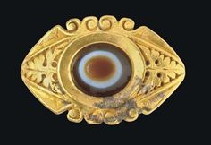 A ROMAN GOLD AND EYE AGATE FINGER RING CIRCA 2ND-3RD CENTURY A.D. The solid cast hoop flat on the interior, angled on the exterior, the outer edges of the lower portion of the hoop with a raised molding of scrolls expanding to openwork volutes, the triangular shoulders each decorated with a pierced-work vine leaf and tendrils, the outer edges of the oval bezel framed by pairs of volutes, set with a bevelled oval eye agate: