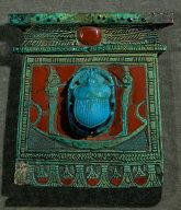 Scarab Pectoral of the Chief Ointment-maker Pa-nehersj. Two goddesses, Isis and Nephtys, Praying to the Scarab as a Symbol of the Sungod Ra. The Scarab is seen in its Morning-Shape of Chepre, a Symbol of Rebirth. Carnelian & Faience. New Kingdom, Circa 12 B.C. Aegyptisches Museum, Staatliche Museen, Berlin, Germany.