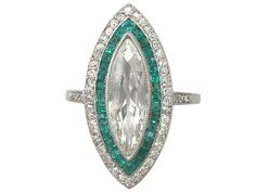 This French emerald and diamond ring is a unique take on a gemstone engagement ring...you could just get lost in that central marquise cut diamond