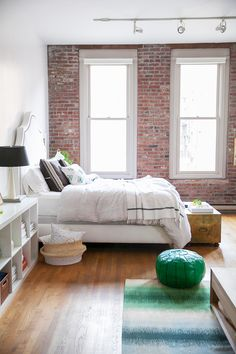 A bright bedroom with exposed brick walls and white bedding