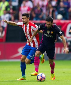 Arda Turan of FC Barcelona duels for the ball with Sergio Alvarez of Real Sporting de Gijon during the La Liga match between Real Sporting de Gijon...