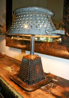 "This lamp is really unique! The base was created from a recycled stove top toaster and the ""lampshade"" is an old colander…"