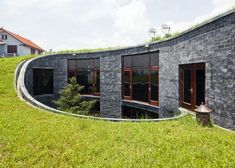 This spiralling stone house in Vietnam has grass on its roof and an oval courtyard at its centre.