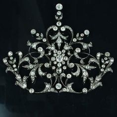A Belle Époque diamond jewel, circa 1890-1900. Set to the centre with a cluster of old brilliant-cut diamonds in millegrain rubover collet settings, within an openwork scrolling surround of stylised foliage set with old brilliant and rose-cut diamonds, with old brilliant-cut diamond bud detail, mounted in silver and gold, diamonds approximately 7.50 carats, length 8.6cm., mounted as a pendant, formerly the centrepiece of a tiara.
