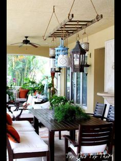 Outdoor patio: LOVE the collection of lanterns hanging from the suspended ladder!