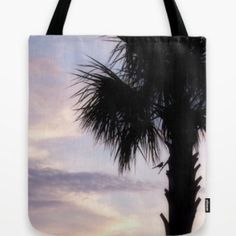 """Tropical palm tree silhouette tote bag Tote bag featuring my original photograph of a Palm tree at sunset, hand sewn from a lightweight poplin fabric. The photograph is print on both sides of the tote, and is finished with a 1"""" wide black cotton strap. Bags Totes"""