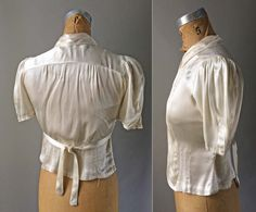 Gorgeous 1940s vintage short collar silk blouse features real pearl buttons, and a stunning pleat detail on bodice, like a tuxedo. Liquid silk satin fabric shimmers with multiple tones based on light and shadow: grey, dark cream, ivory, ecru, white. Original Belt ties at front or back. Some as-is issues, overall lovely. Extra small. APPROXIMATE MEASUREMENTS TAKEN LYING FLAT: Shoulders: 13 Bust: 17 Waist: 14 Length: 18   CONDITION: Fair condition. Some stains or scuffs on front in dark grey…