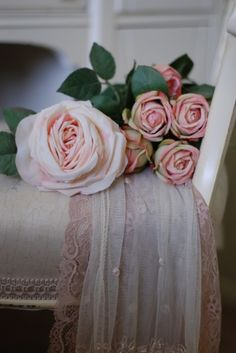 Pink flowers laying on shabby chic bench with pink sheer fabric