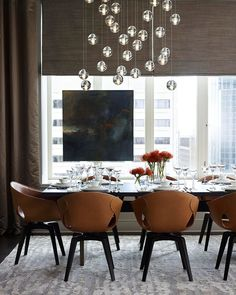 "Get The Hollywood Look - Traditional Home® ~ In the dining room, a chandelier by Bocci serves as the graphic focal point above the table, appointed with white china and Baccarat crystal. The space takes full advantage of the apartment's wonderful view of the Chicago skyline. Janette Kerr's ""Fragments of Fire"" painting hangs on the window for an unexpected touch.  #design #interior #interior_design"