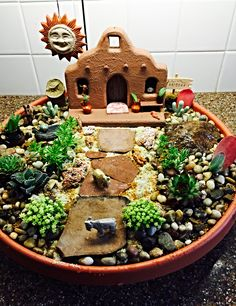 Southwestern Succulent Garden - Multiple succulents amid a variety of terra cotta accessories, miniature animals and tiny pebbles with sand ground cover.