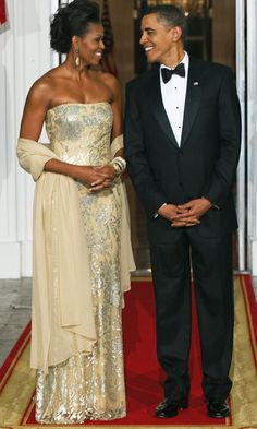 November 2009   The Obamas share a loving look before greeting their guests for their first State Dinner. Michelle stuns in this strapless pale yellow gown and matching wrap.