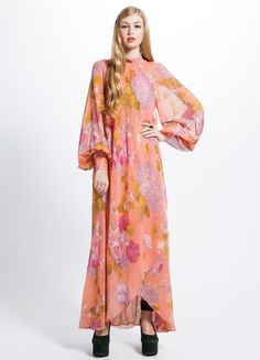 "Stunning 70's all silk floral print dress featuring great cut, blousy, cuffed sleeves and beautifully draped back.  Center back zipper entry.    Condition: Excellent  Label: N/A  Marked Size: N/A  Fabric: Feels like polyester  Color: Peach  Bust: 32""  Waist: 28""  Hips: 38.5""  Length: 56"""