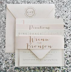 This is our Bronson wedding invitation suite with a belly band. In the sample photos we have used ivory and peachy pink metallic cardstock with gold and
