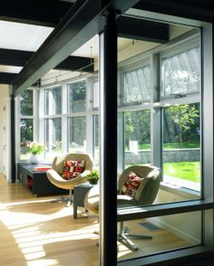 Sunroom - black beams contrasting with light floors and green outdoors