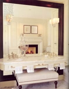 Beautiful fireplace, Carrera marble vanity. Bench probably sits in front of the fireplace. Lovely room.