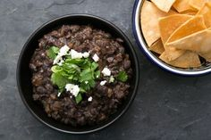 Refried Black Beans: 1 lb dry black beans 1 Tbsp olive oil 1/2 teaspoon ground cumin 1/2 large white onion, chopped (about 1 1/2 cups) 1 garlic clove, minced 2 teaspoons salt 1/2 cup chopped fresh cilantro (leaves and tender stems) 1 teaspoon chipotle chili powder 1 teaspoon chili powder 1/2 teaspoon ground cumin 1/2 large white onion, chopped (about 1 1/2 cups) 1 garlic clove, minced Green onion Cilantro Crumbled cotija or queso fresco cheese Tortilla chips or corn tortillas