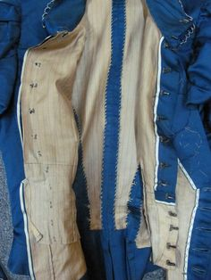 Inside of a teal silk Late Victorian Bodice, showing striped cotton lining, hooked panel to close at the waist, whip stitched edges to finish the seams and the selvedge edge used on the straight bodice front