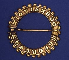 14th cent British Museum. From England. Annular brooch; gold; flat band with knobs round outer edge; chased legend. Gold.