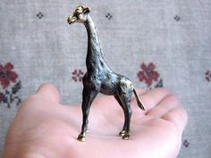 Cute giraffe figurine made entirely of antiqued bronze with black patina.  Size: 6*4*1 cm (2,36*1,57*0,39 in)