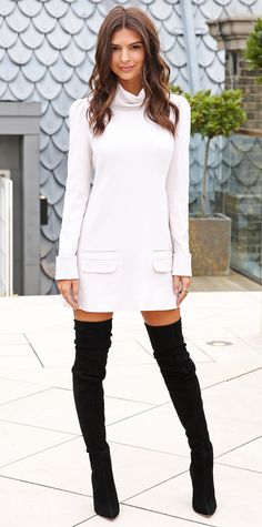 Emily Ratajkowski in a pale turtleneck long-sleeve shift with thigh-high black suede boots.