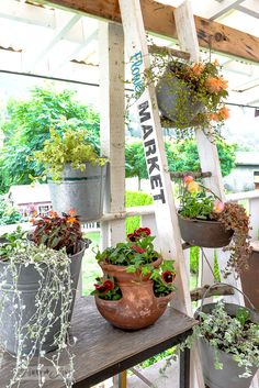 Flowers in galvanized buckets hanging from a nature inspired branch ladder plant stand / funkyjunkinteriors.net