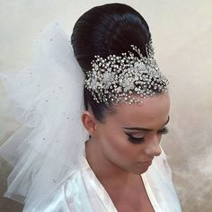 Closeup of our gorgeous bride Victoria and her stunning updo adorned with a crystal-encrusted headpiece and veils from our bridal accessory boutique!
