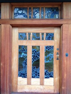 A look at the detail of the triple front door and transom. A Japanese black pine motif is present in plated leaded art glass, highlighting the Asian influence throughout the house.