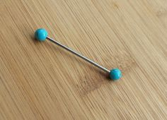 This unique industrial barbell has two turquoise ends. Totally unique and native, youre sure to have a beautiful scaffold piercing with this