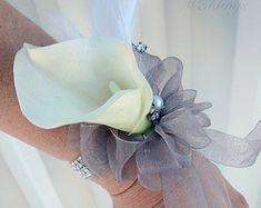 Ce corsage de mariage classique calla lily / ensemble de fleur à la boutonnière est une belle touche de finition pour toute occasion solennelle, des mariages ou des bals de finissants. Ce corsage et une fleur à la boutonnière sont conçus avec un lys de calla blanc crémeux real touch, herbe boucles et détail de ruban de cisaillement à la fin. Le corsage et une fleur à la boutonnière sont les deux broches. Chaque lis calla mesure 3(8 cm) de haut par 2 (5 cm) de large 2 pces comprend…