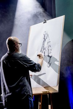 Mike Mignola at work doing a sketch of his character Hellboy.
