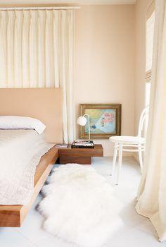 Sheepskin rug on floor of bedroom with white chair in corner