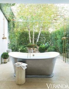 The rolling hills of Ojai set the scene for this beautiful and simple bath and shower area in a charming retreat, which gracefully brings the greenery of the outdoors to a bathroom setting. The tub is by The Bath Works and the faucet and shower fixtures are by Waterworks.