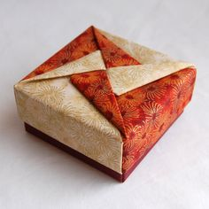 http://www.fabricorigami.com Example from: Fabric Origami Pinwheel Box - Rust. $5.00, via Etsy.